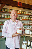 Portrait of a senior man standing with spice jar in store