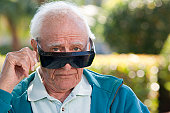 Portrait of a senior man wearing cataract dark glasses