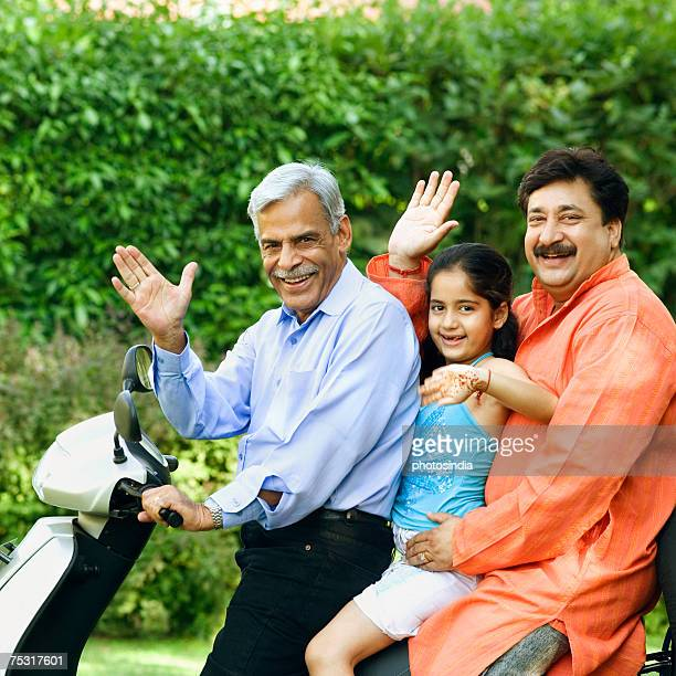 Portrait of a senior man with his son and granddaughter riding a motor scooter