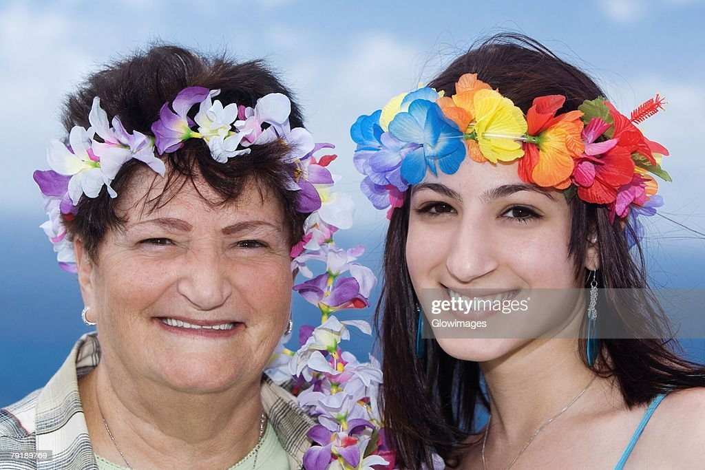 Portrait of a senior woman and her daughter wearing flowers : Foto de stock