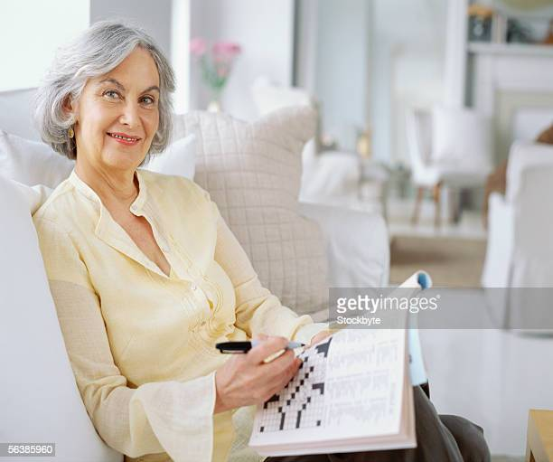 portrait of a senior woman doing a crossword puzzle