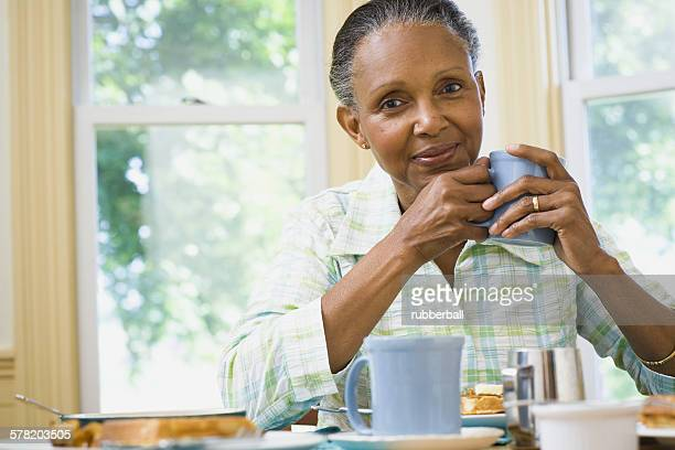 Portrait of a senior woman holding a cup of coffee at the breakfast table