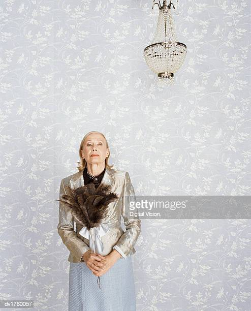Portrait of a Senior Woman Holding a Feather Duster Standing Below a Chandelier