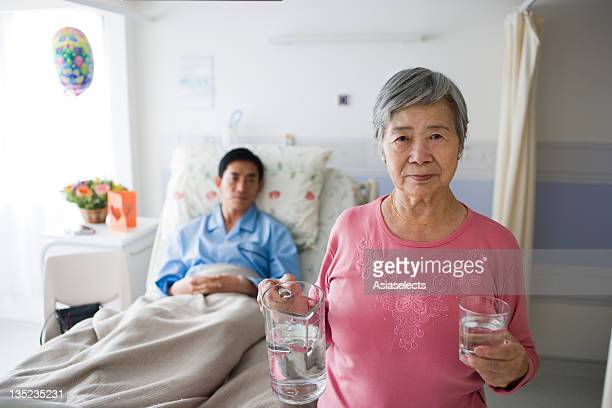 Portrait of a senior woman holding a glass of water with a male patient in the background