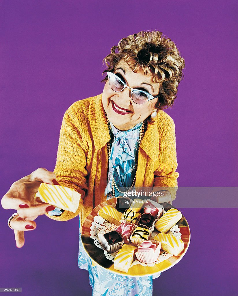Portrait of a Senior Woman Holding a Tray of Cakes : Stock Photo