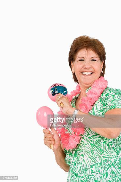 Portrait of a senior woman playing maracas and smiling