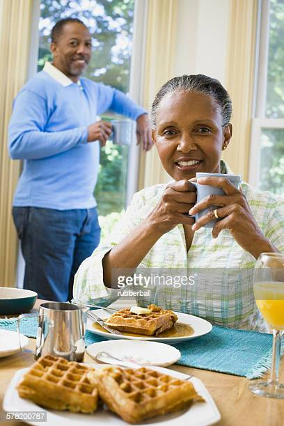 Portrait of a senior woman sitting at the breakfast table with a senior man standing behind her