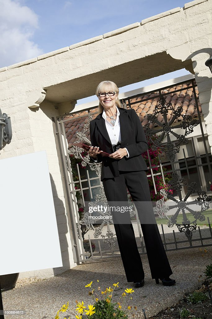 Portrait of a senior woman standing with clipboard in front of entrance gate : Stock Photo