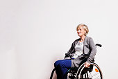 Portrait of an unhappy senior woman with wheelchair in studio. Copy space.