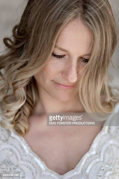 portrait of a sensual beautiful women in her early thirties with long blonde hair, blue eyes and freckles photographed on her wedding day in white wedding dress - looking dreamy