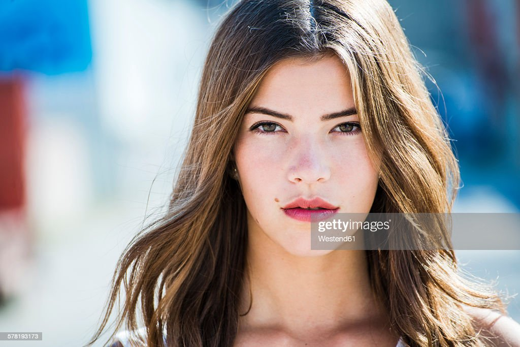 Portrait of a serious brunette young woman outdoors