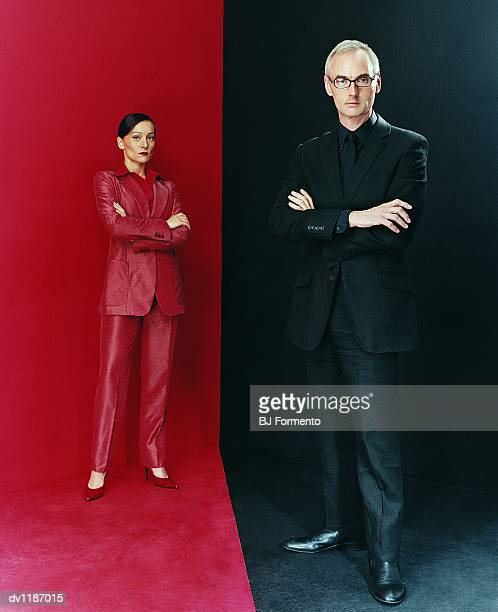 Portrait of a  Serious Businessman and a Businesswoman Dressed in Red and Black Suits