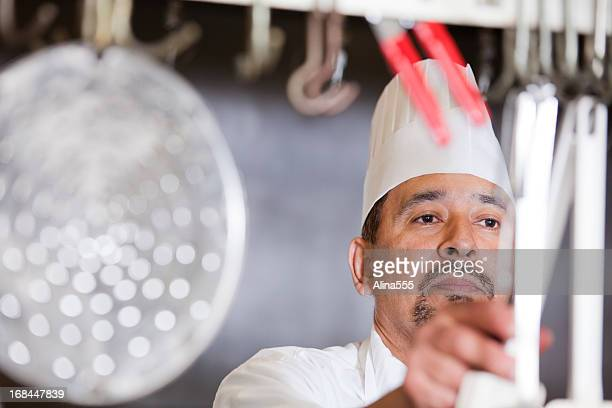 Portrait of a serious busy cook inside the restaurant kitchen