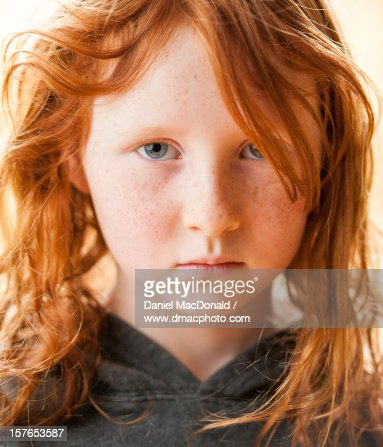 Portrait of a serious young girl with red hair