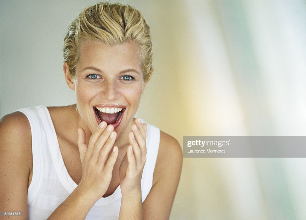 Portrait of a shocked and laughing young woman : Stock Photo