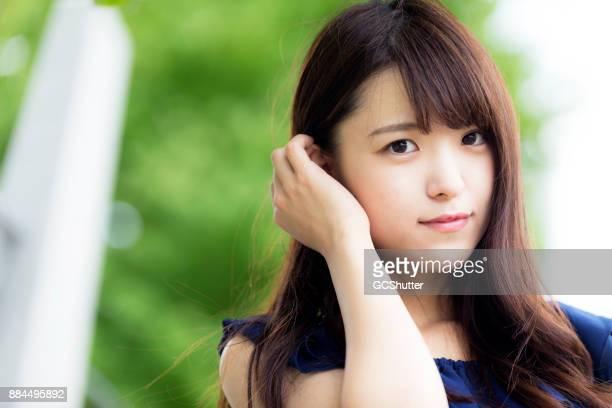 柔らかい緑の背景に対してシャイな日本の肖像画