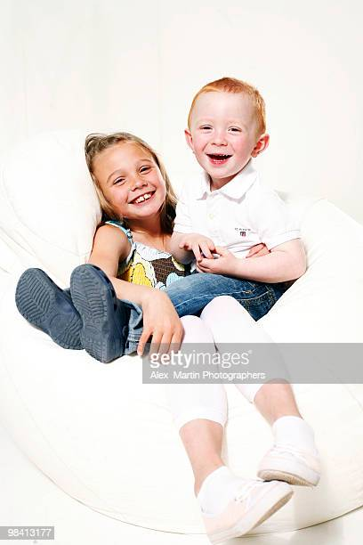 Portrait of a sister and brother against a white background.
