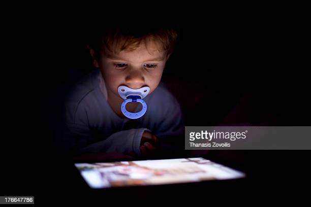 Portrait of a small boy looking a tablet in the da