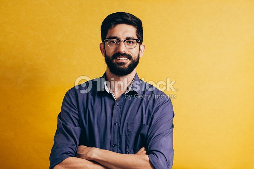 Portrait of a smiling bearded man in eyeglasses looking at camera isolated over yellow background : Stock Photo