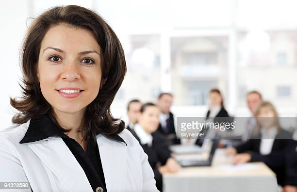 Portrait of a smiling brunette woman at business meeting.