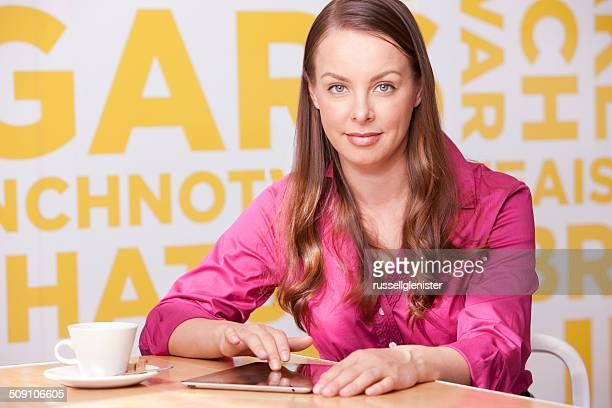 Portrait of a smiling businesswoman in office working on tablet during tea break