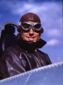 Portrait of a smiling Captain Marion Carl USMC in the cockpit of an airplane wearing leather jacket helmet and flight goggles at the Naval Air...