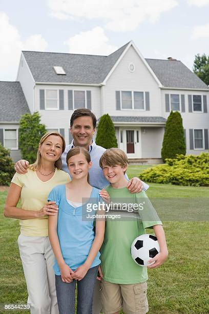Portrait of a smiling family by house
