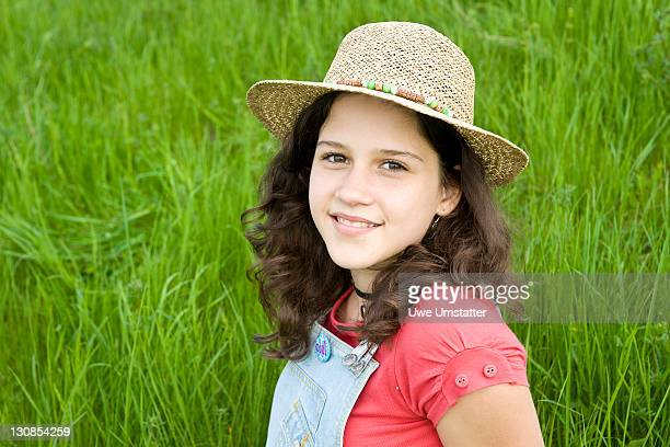 Portrait of a smiling girl wearing a sun hat on a meadow