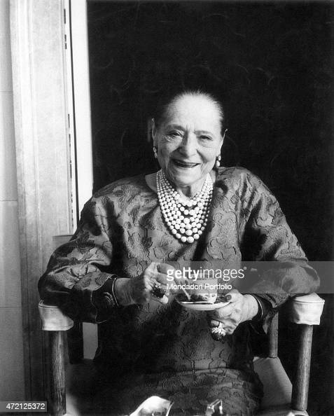 'Portrait of a smiling Helena Rubinstein seated on a chair with a china cup in hand the famous Polish born American entrepreneur of cosmetics...