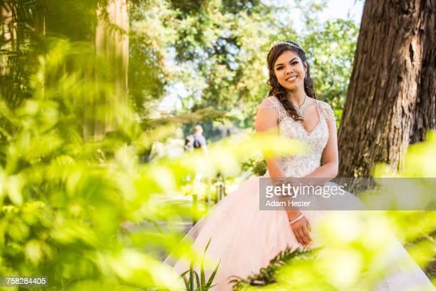 Portrait of a smiling Hispanic girl wearing gown near foliage