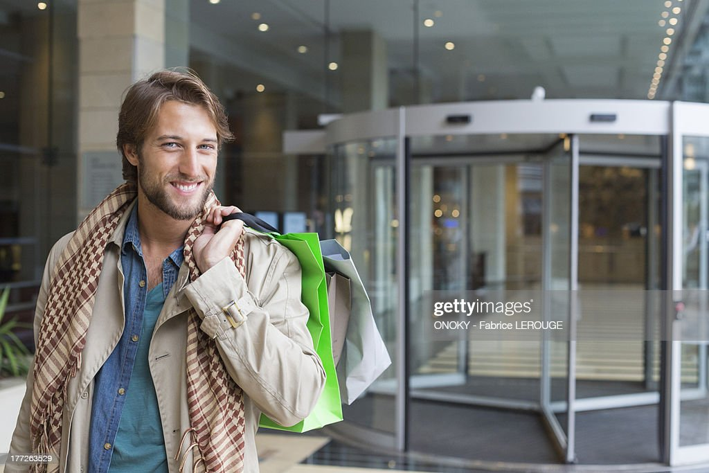 Portrait of a smiling man carrying shopping bags on his shoulders