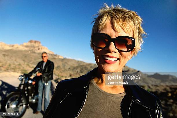 Portrait of a Smiling Mature Woman in the Desert Wearing Sunglasses, Man in the Background Standing by a Motorbike