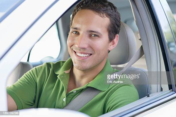 Portrait of a smiling mid adult man driving a car