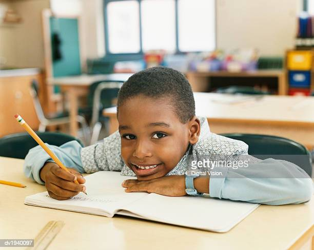 Portrait of a Smiling Schoolboy Sitting at a Table and Resting His Head on a Exercise Book