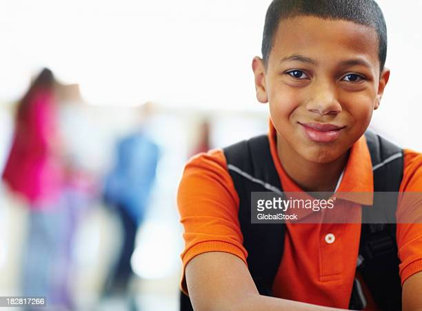 Portrait of a smiling schoolboy with friends in the background