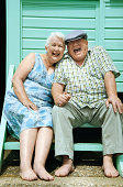 Portrait of a Smiling Senior Couple Sitting on the Steps in Front of a Beach Hut