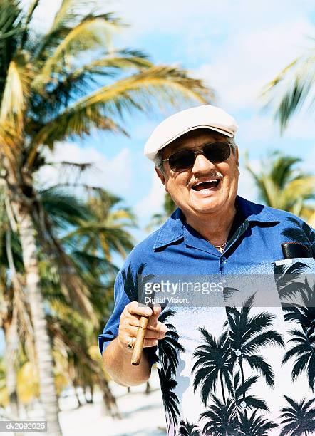 Portrait of a Smiling Senior Man Wearing a Hawaiian Shirt and Smoking a Cigar