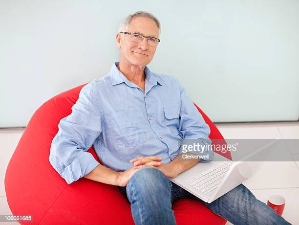 Portrait of a smiling senior man with laptop