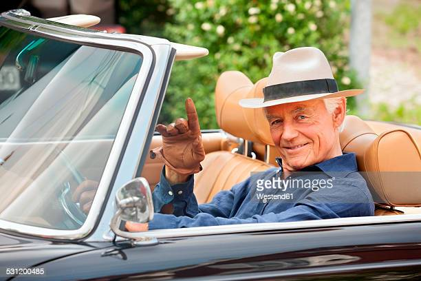 Portrait of a smiling senior sitting in a convertible car waving