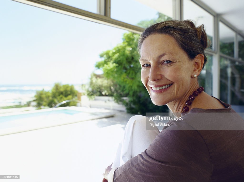 Portrait of a Smiling Senior Woman Sitting by Open Patio Doors : Stock Photo