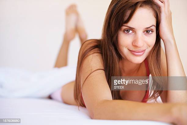 Portrait of a smiling sexy female lying on bed