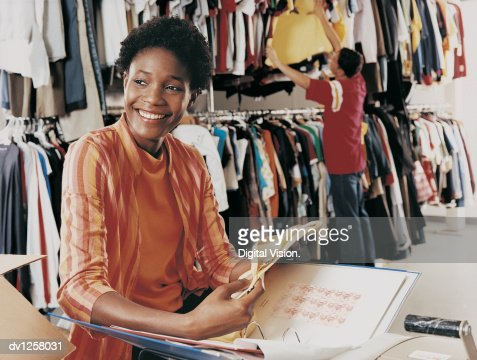 shop assistant standing in the storage room of a clothes shop with    similar images