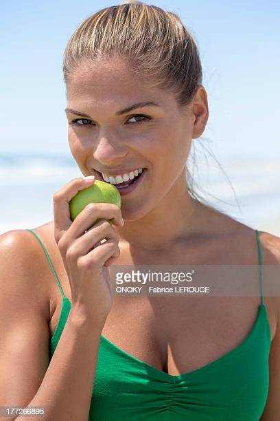 Portrait of a smiling woman eating a green apple