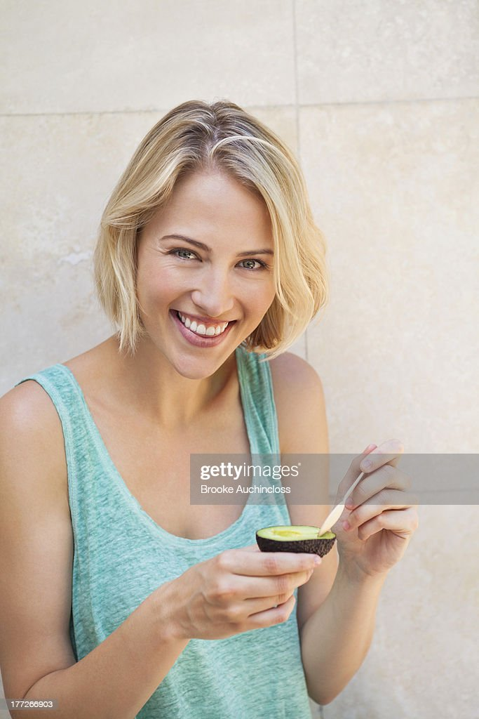 Portrait of a smiling woman eating avocado