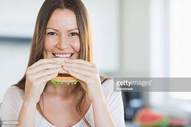 Portrait d'une femme souriante manger un sandwich en cuisine