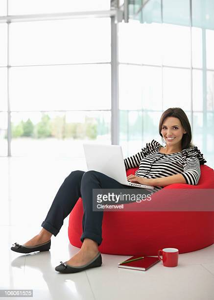Portrait of a smiling woman sitting on a bean bag with laptop