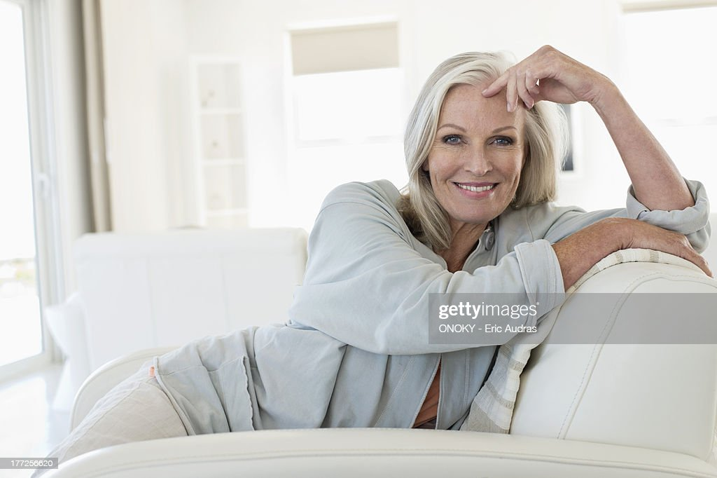 portrait of a smiling woman sitting on a couch stock photo. Black Bedroom Furniture Sets. Home Design Ideas