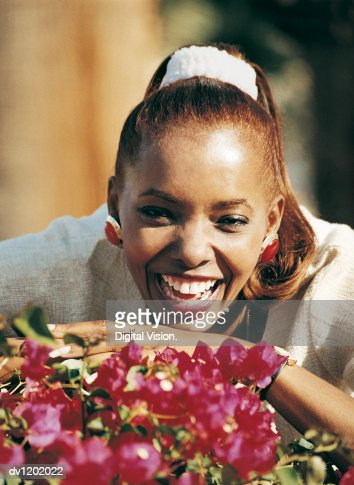 Portrait of a Smiling Woman With Her Arms Crossed Behind Some Red Flowers