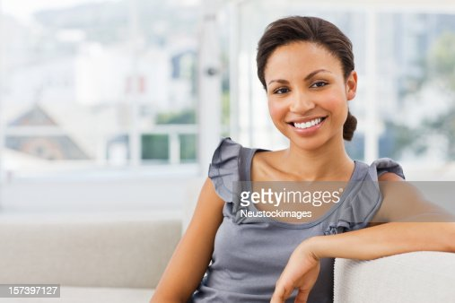 Portrait of a smiling young lady sitting on couch : Stock Photo