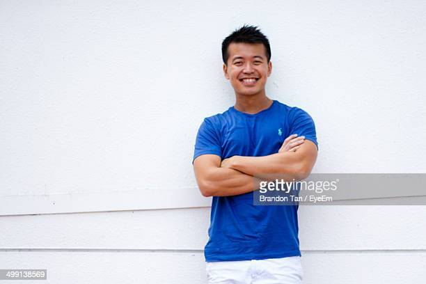 Portrait of a smiling young man with arms crossed